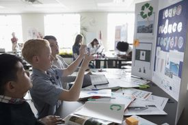 Boy middle school student photographing science project poster with camera phone in classroom