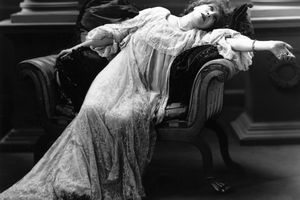 Actress Sarah Bernhardt reclines onstage in theatrical performance
