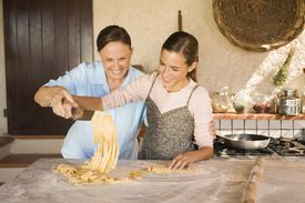 Grandmother and granddaughter unraveling fresh tagliatelle with knife , Italy