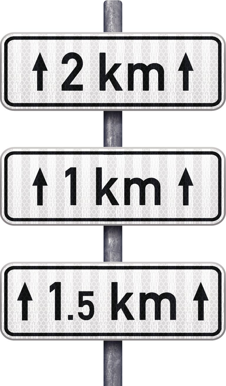 White traffic signs indicating distance ahead (metric)