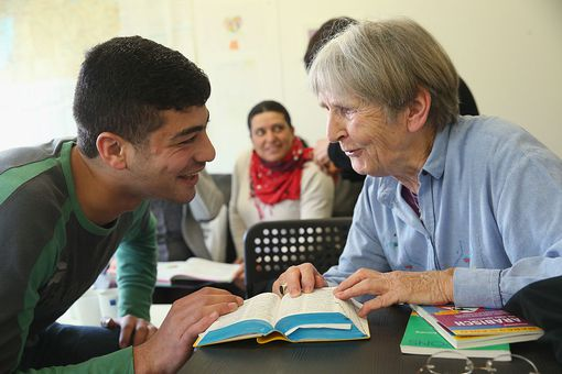 Older person and younger person discussion something with dictionary in front fof them.