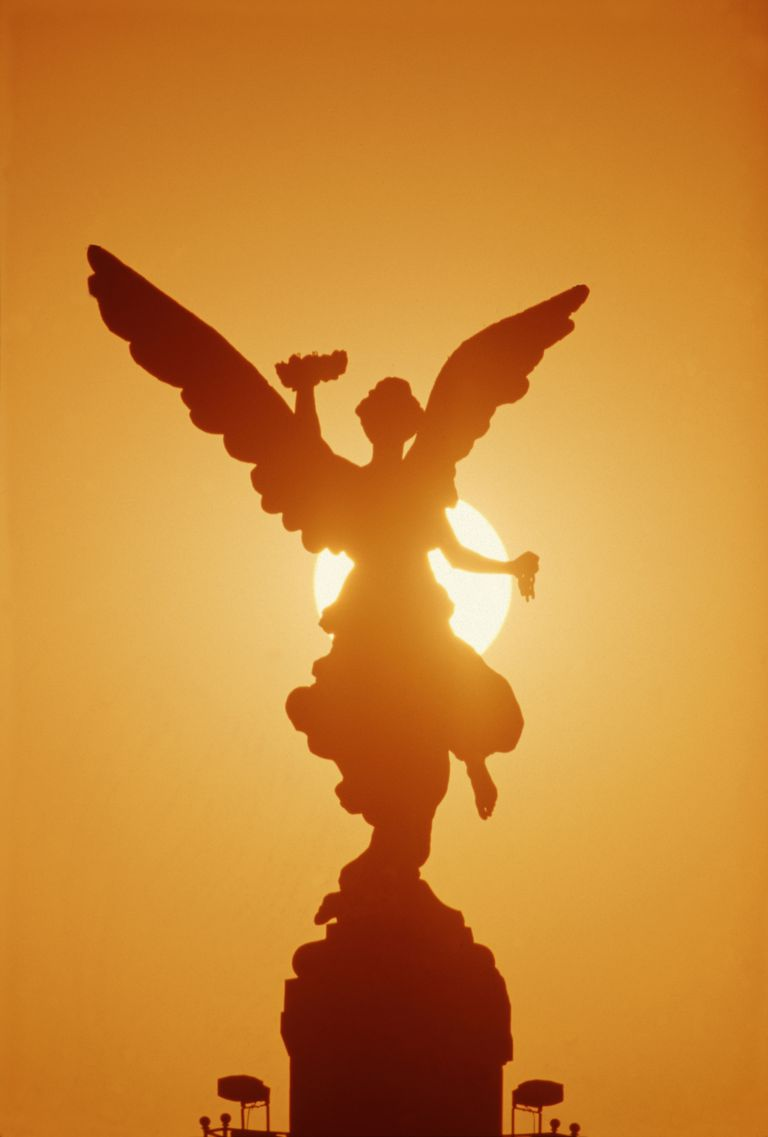 archangel statue silhouetted againsted sun