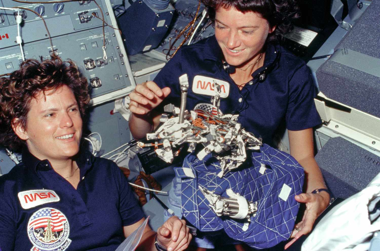 Sally Ride and Kathryn Sullivan show sleep restraint on space shuttle.