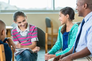 School counselor talks with diverse elementary students