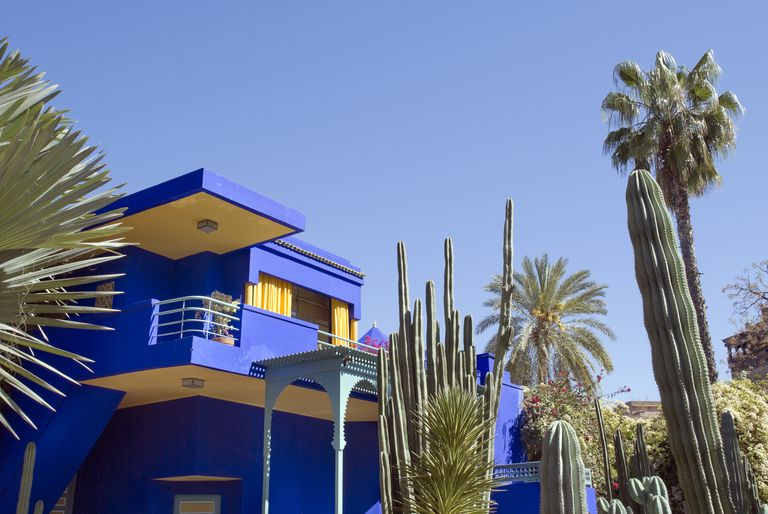 Colorful Marine Blue House With Light Posts And Bright Yellow Outdoor Ceilings Surrounded By Majorelle