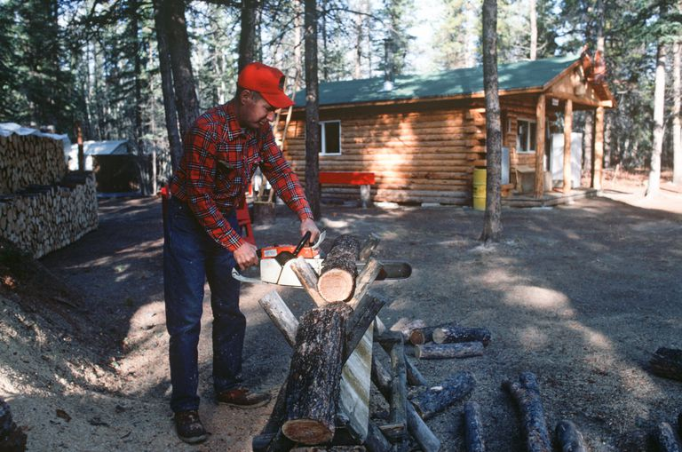 man in red flannel shirt and red hat sawing logs with a chain saw near a log cabin