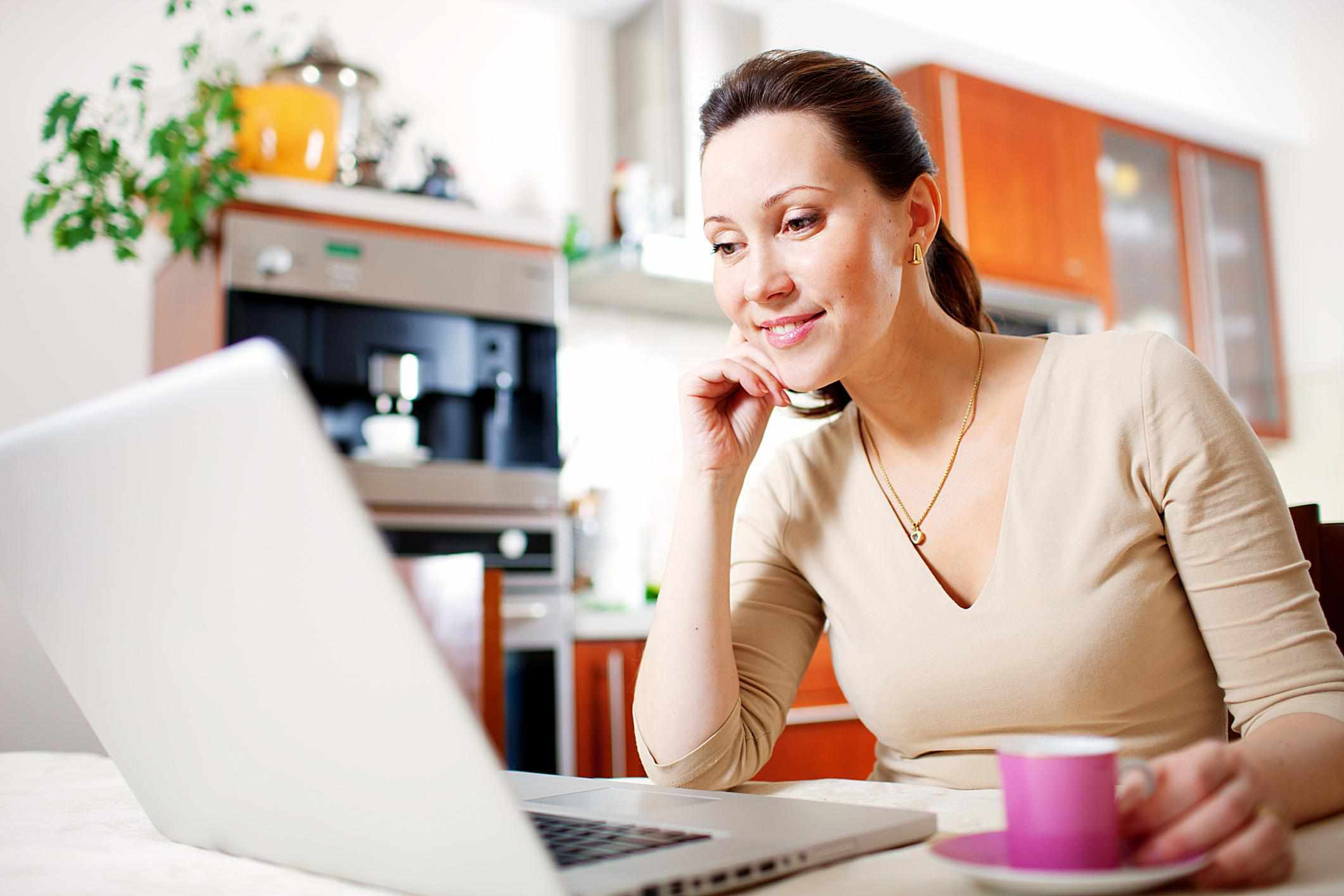 Woman looking at laptop on desk.