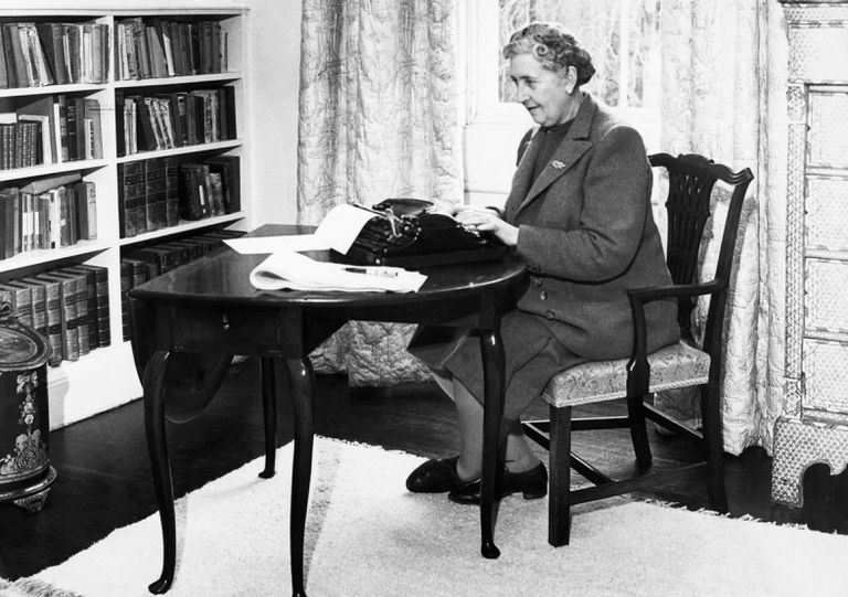Agatha Christie writing at her desk at a typewriter
