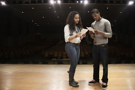 two kids on stage reading a script