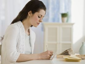 Woman writing thank you notes at table