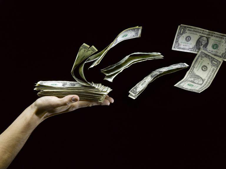 Mano con fajo de billetes de dólar que se echan a volar