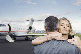 man and woman hugging in front of airplane