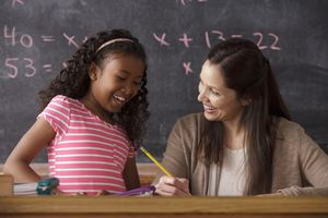 A girl and her teacher working on math.