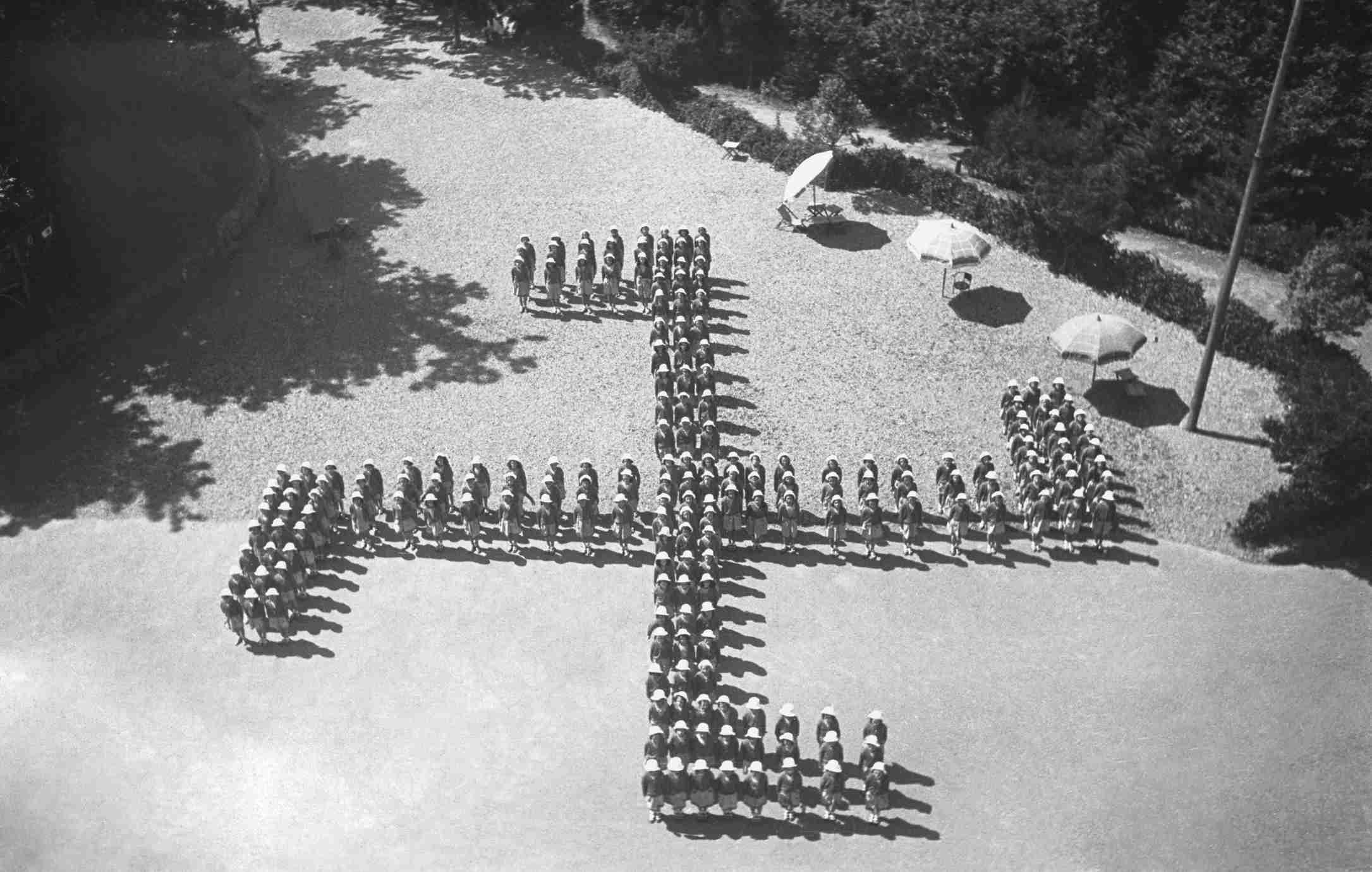Italian girls' summer camp making up a Nazi swastika, August 8, 1942, Genoa, Italy.