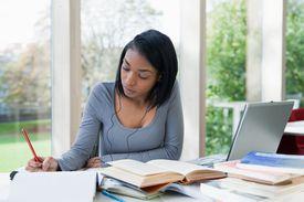 university student writing at desk