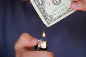 Person burning dollar note