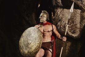 Powerful gladiator posing on rocks