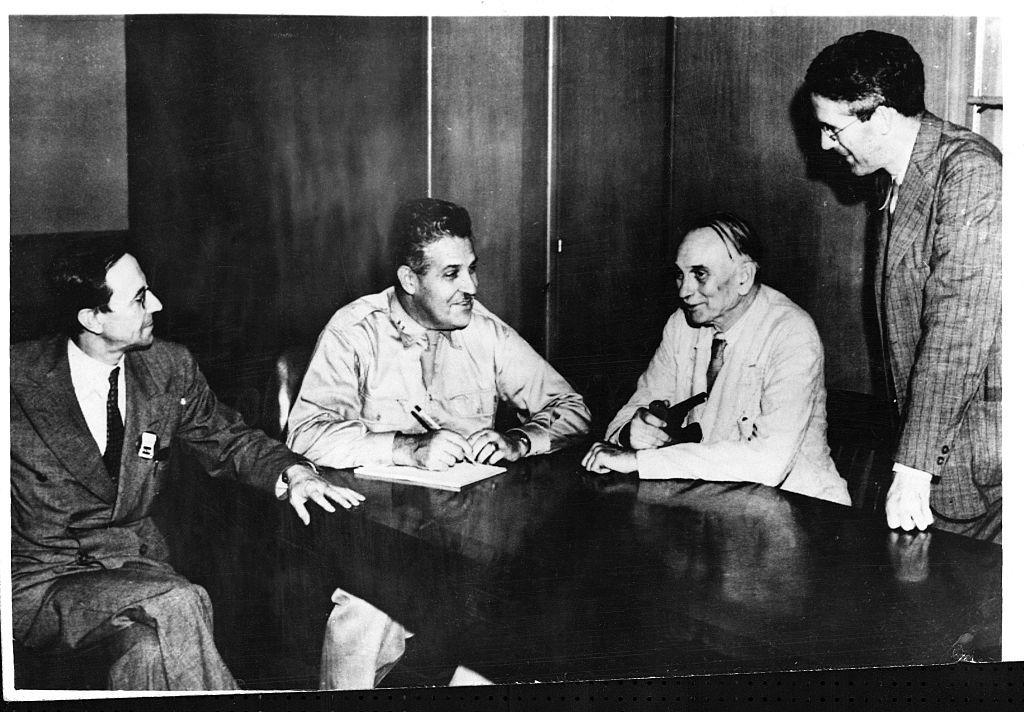 four men sit around a table