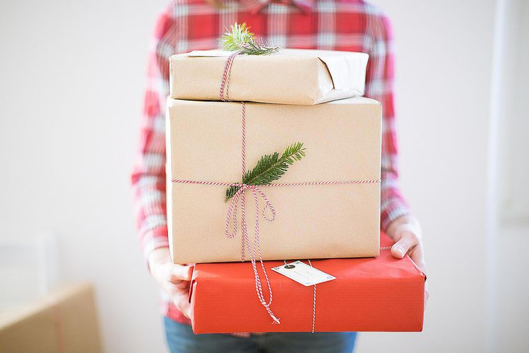 A woman carries three tastefully wrapped gifts. Most of us participate in Christmas gift giving, which creates a lot of waste every year.