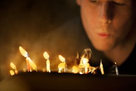A Man Blows Out Candles
