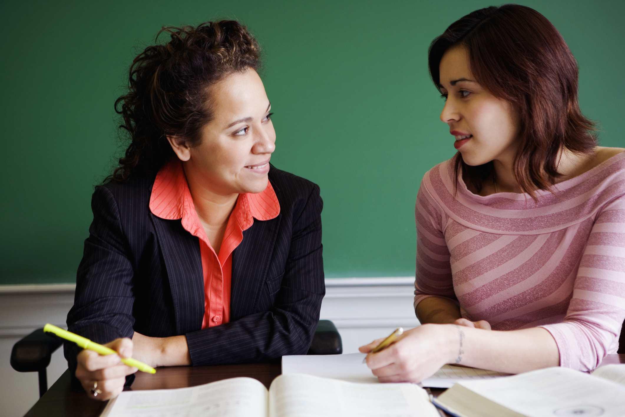 Estudiante y profesor hablando en un aula.