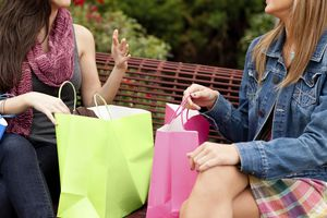 Two Happy Young Women with Shopping Bags Sitting at Mall