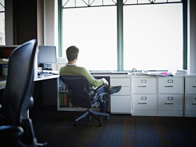 Businessman sitting in chair at desk rear view