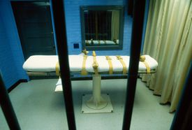 Lethal injection table with straps as seen through barred window