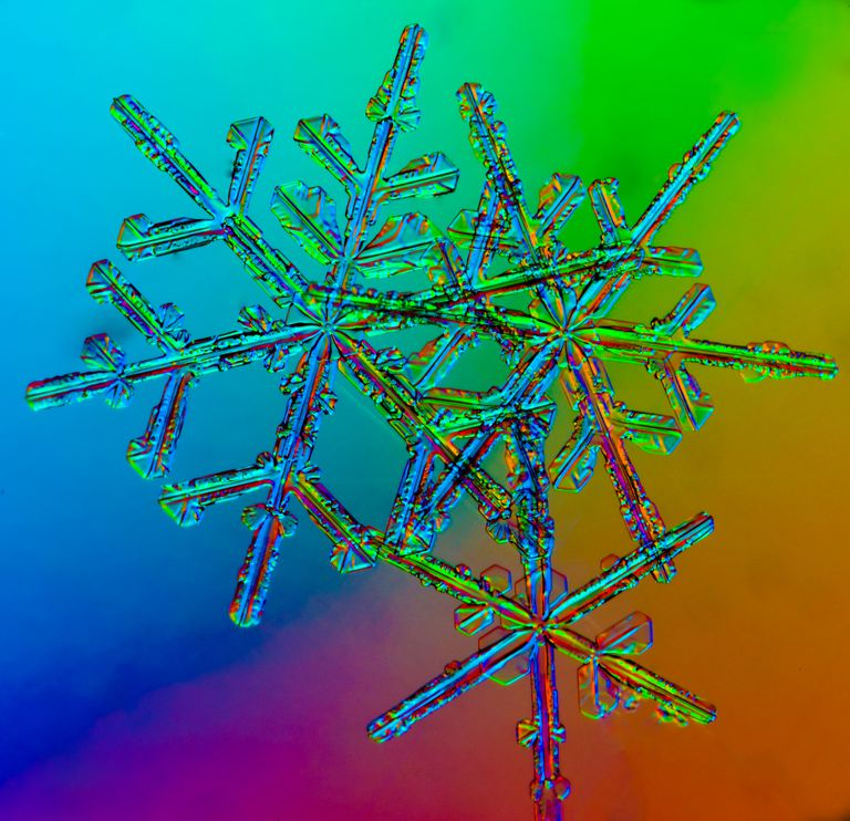 Snowflakes against a rainbow colored background.