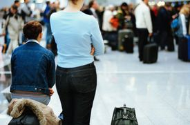 Women with luggage at airport, rear view