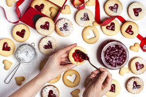 Traditional Linzer cookie with strawberry jam, top view. Female hands making cookies.