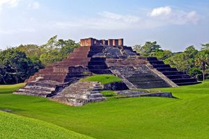 Ruins of a Mayan brick pyramid surrounded by bright green grass on a sunny day.