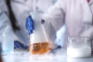 Scientist holding a flask with evaporating liquid