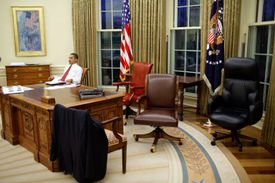 President Barack Obama sitting behind the Resolute Desk in the Oval Office.