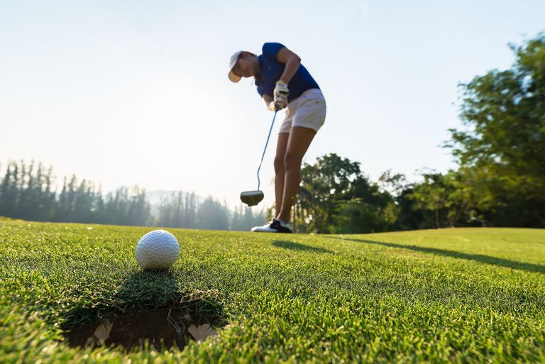 Asian woman golfer action to win after long putting golf ball on the green