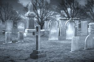 Black and white image of headstones in a cemetery.