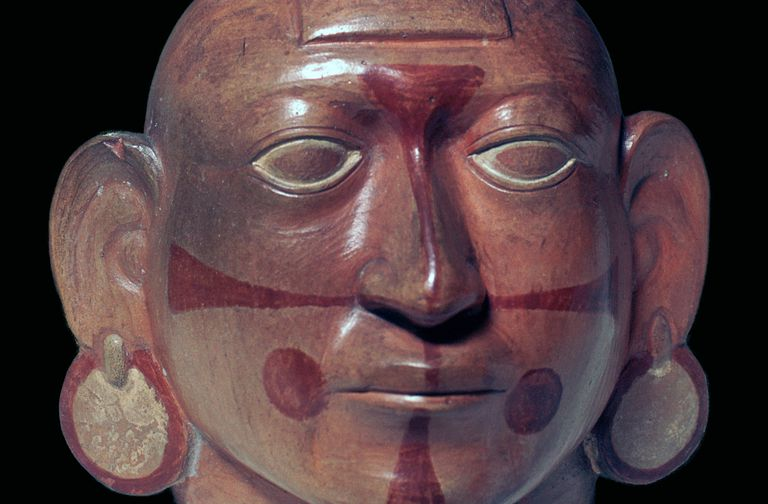 A cropped close-up of a Mochicha stirrup-spout vessel of a bald man wearing face-paint and earrings.