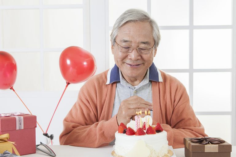 Senior man making birthday wish with eyes closed,