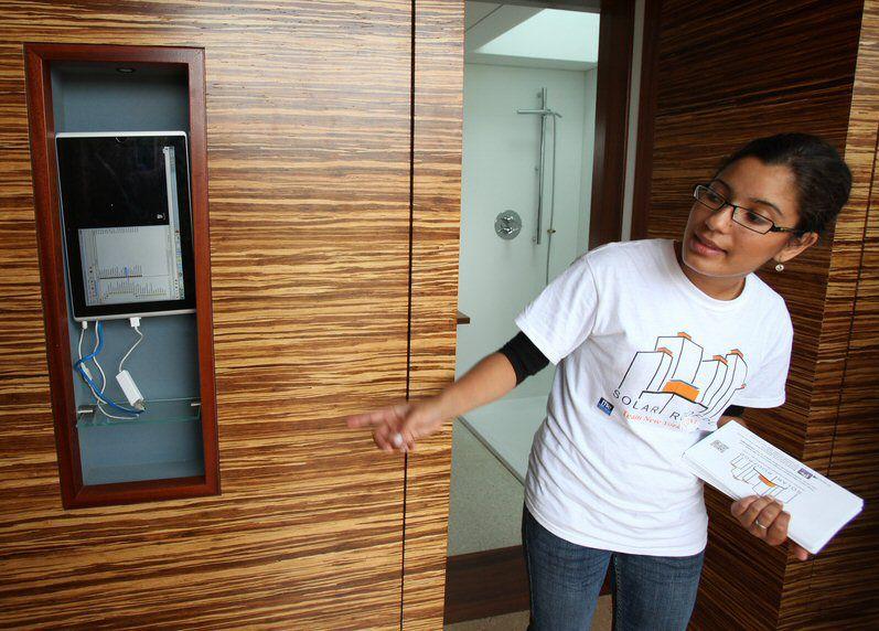 Étudiant Yinery Baez explique un panneau de contrôle à écran tactile à l'intérieur de la maison solaire de l'équipe.