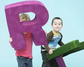 two kids, one holding up large letter R