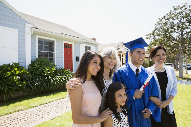 Smiling graduate and multi-generation family front yard