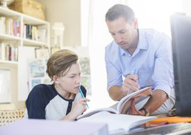 Father helping teenage son with his homework
