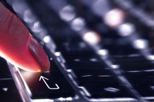Finger touching enter sign on keyboard