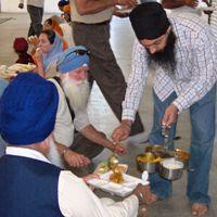 A singh performing langar seva, serving seconds helpings to the sangat.