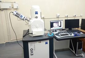 Electron microscope and computer equipment in a laboratory environment.