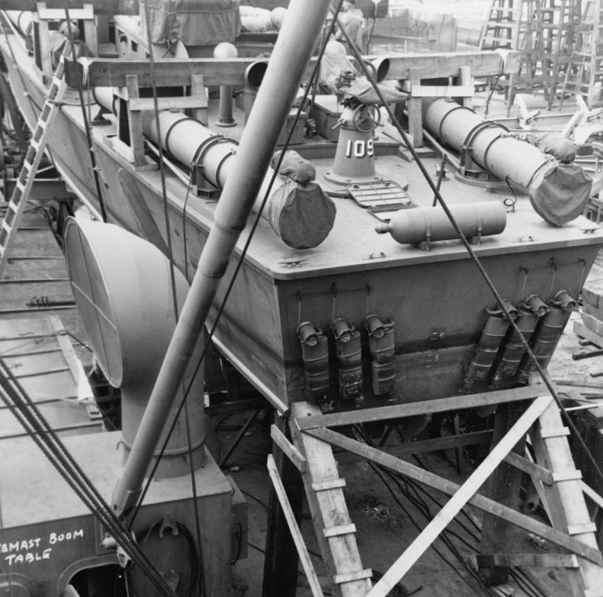 Stern of PT-109 aboard a cargo ship with six mufflers visible and timber bracing for the voyage to the Pacific.