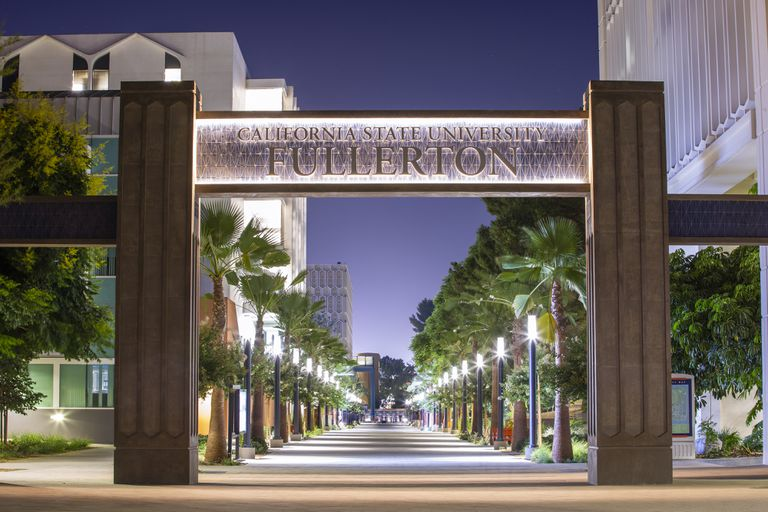 "A sign reading ""California State University Fullerton"" stretches above and across a palm tree lined walkway"