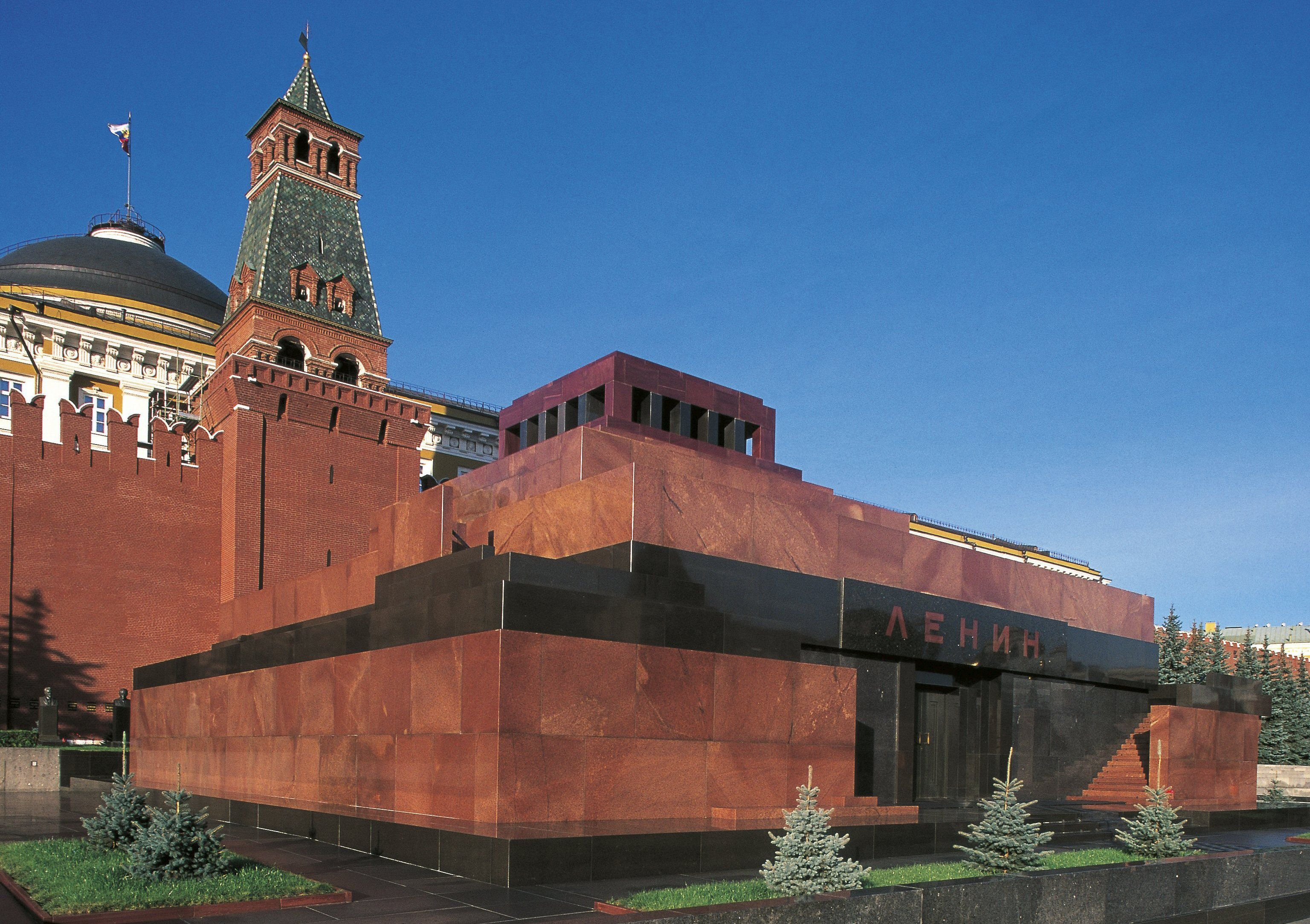 red stone fortress-like structure integrated into a red wall surrounding a towered Kremlin