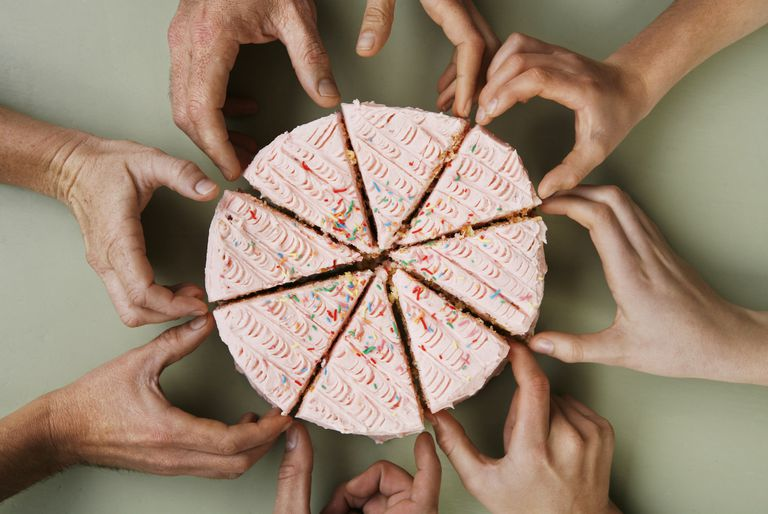 Eight hands reach for a slice pink frosted cake that's ready to be shared
