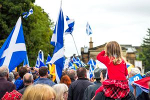 Scottish flags wave over a crowd of Scots and tartan